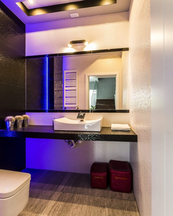 Bathroom with modern amenities, wide mirror and blue ceiling backlight