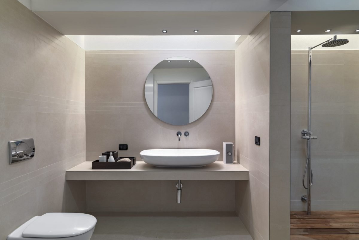 interiors of a modern bathroom in the foreground the countertop sink while the walls are covered in pink marble on the right side there is a masonry shower cubicle
