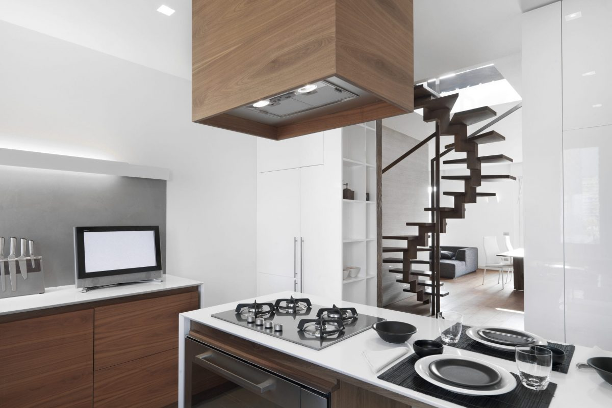 interior shooting of a modern kitchen in foreground the island kitchen  with gas hob on the backgrund  the libing room with staircase