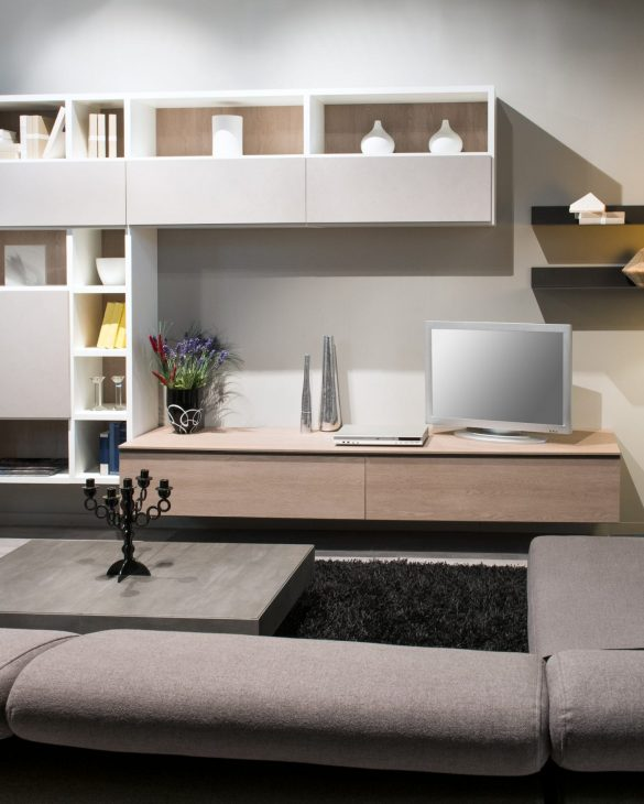 Modern living room interior with comfortable upholstered brown sofas facing a display cabinet and television illuminated by down lights and a lamp